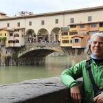 Clare rests on a wall on the Arno River with the Ponte Vecchio in the background.